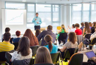 Bild bakifrån på personer som sitter och lyssnar på ett seminarium